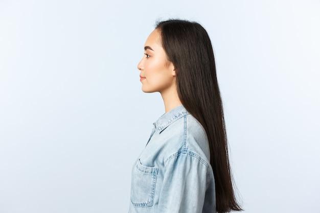 Образ жизни, эмоции людей и понятие красоты. профиль красивой корейской девушки с длинными темными волосами, смотрящей влево, стоящей прямо в повседневной одежде, посещение салона красоты парикмахера