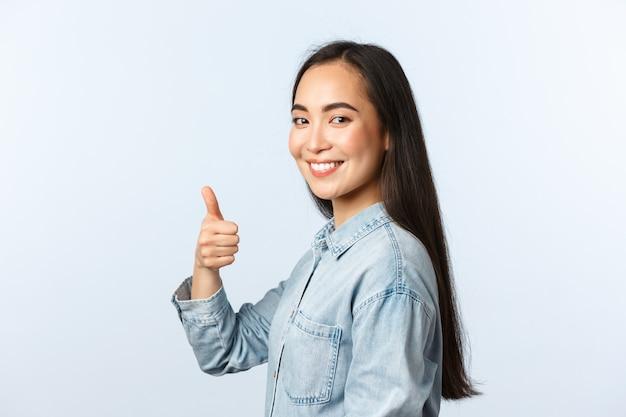 Образ жизни, эмоции людей и понятие красоты. профиль поддерживающей подруги, корейской девушки в повседневной одежде, поворачивает камеру, чтобы показать большой палец в знак одобрения, гарантии или рекомендации качества, рекламы.