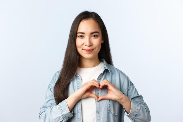 ライフスタイル、人々の感情と美しさの概念。笑顔の素敵なアジアの女性は、何かのように、愛や同情を告白します。白い背景に立って、胸にハートのサインを示す女の子。