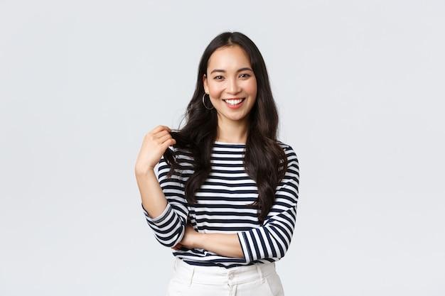 Образ жизни, эмоции людей и повседневная концепция. очаровательная улыбающаяся корейская девушка в полосатой рубашке, трогающая прядь волос и счастливо улыбаясь в камеру, разговаривает с другом, белый фон