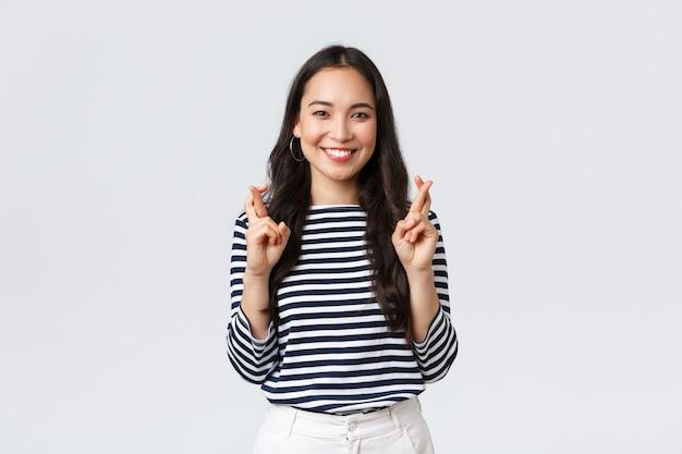 라이프 스타일, 사람들의 감정 및 캐주얼 개념. 희망에 찬 흥분된 귀여운 한국 여성은 손가락을 꼬고 웃고, 긍정적인 소식을 기대하고, 꿈이 이루어지기를 간청합니다.