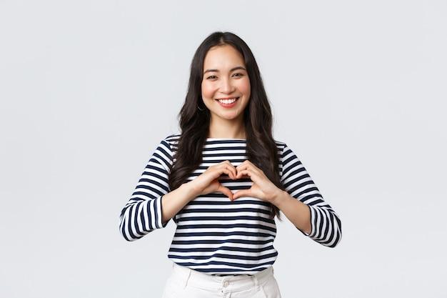 ライフスタイル、人々の感情、カジュアルなコンセプト。ハートのサインを示して笑顔、同情やケアを表現し、白い背景に立っている素敵な笑顔の愛らしいアジアの女性