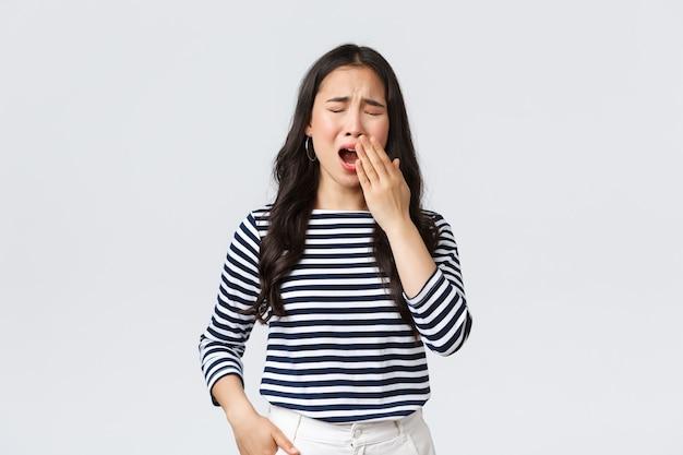 ライフスタイル、人々の感情、カジュアルなコンセプト。オフィスで遅くまで働き、目を閉じてあくびをしている眠そうな疲れた女性は、悪くなりたいです。アジアの女の子は早く目が覚めた、コーヒーが必要、白い背景に立つ