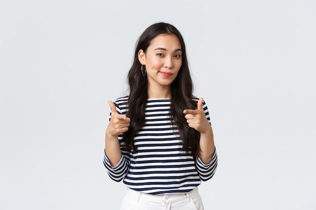 Образ жизни, эмоции людей и повседневная концепция. молодцы, здорово сыграли. довольная и впечатленная азиатская девушка показывает пальцем на камеру, чтобы похвалить вас, подбодрить или поздравить с отличной работой