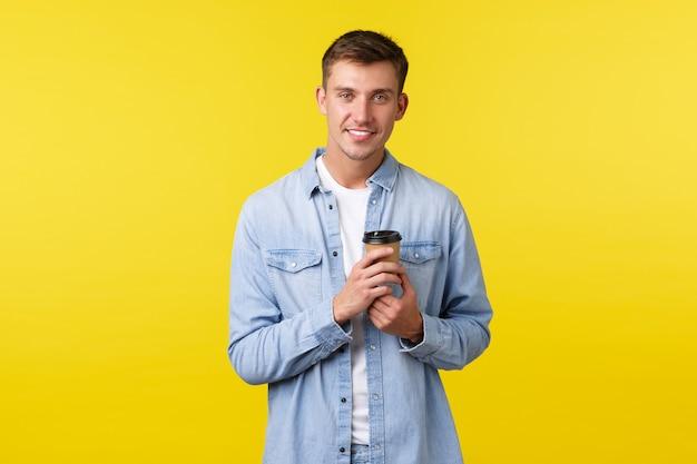 ライフスタイル、人々の感情、レジャーの概念。白い笑顔のハンサムな若い男、カフェでテイクアウトのコーヒーを注文し、紙コップから飲んで、黄色の背景でカジュアルな会話をしています。