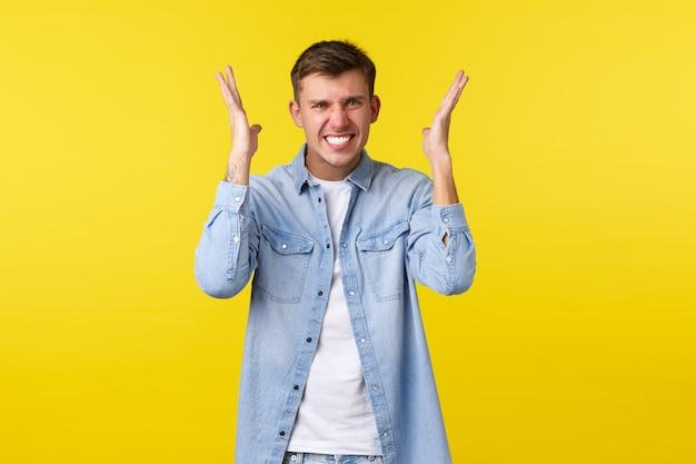 ライフスタイル、人々の感情、夏のレジャーのコンセプト。イライラして腹を立てている金髪のハンサムな男は、狂気になり、気性を失い、手を上げて、イライラした黄色の背景に顔をゆがめます。