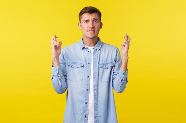 ライフスタイル、人々の感情、夏のレジャーのコンセプト。気になる金髪のハンサムな男は、彼の将来を心配し、願い事をするように指を交差させ、唇を噛み、重要な結果、黄色の背景を待っています。