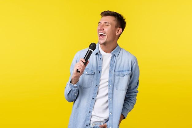 ライフスタイル、人々の感情、夏のレジャーのコンセプト。のんきな幸せな男性歌手、陽気な表情でマイクに向かって歌を歌っている男は、カラオケの夜、黄色の背景に夢中になりました。