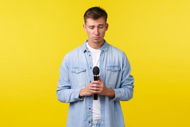 ライフスタイル、人々の感情、夏のレジャーのコンセプト。悲観的で悲しみ、悲嘆に暮れる金髪の男がすすり泣き、マイクを持っているように不安そうに見下ろしている、黄色の背景。
