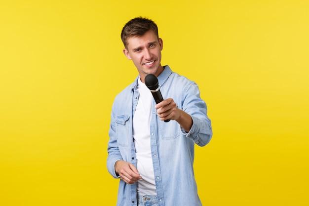 ライフスタイル、人々の感情、夏のレジャーのコンセプト。ハンサムな生意気なブロンドの男のパフォーマーがマイクを手渡し、誰かにインタビューし、生意気な笑顔と黄色の背景に立っています