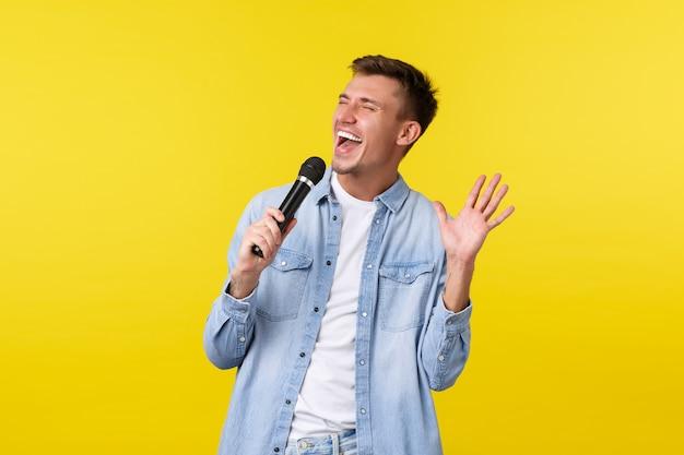 ライフスタイルの人々の感情と夏のレジャーの概念幸せなのんきハンサムな男が情熱を持って歌う...