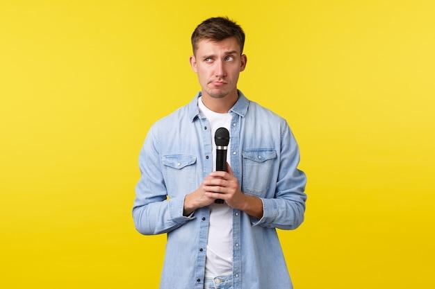 ライフスタイル、人々の感情、夏のレジャーのコンセプト。優柔不断で思慮深いハンサムな男が歌を選び、何が演奏されるかを考え、マイクを持って、ためらいのある黄色の背景を目をそらします。