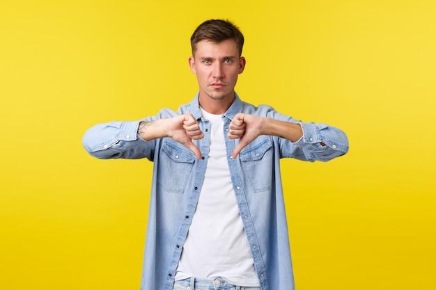 ライフスタイル、人々の感情、夏のレジャーのコンセプト。真面目な心配のハンサムな男は、製品に同意しない、不承認または嫌い、製品が好きではない、黄色の背景として親指を下に向けています。
