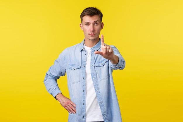 ライフスタイル、人々の感情、夏のレジャーのコンセプト。カジュアルな服装の真面目なゲイの男性は、禁止されている指を振って、不承認になり、人を止めようとします。黄色の背景に制限を与えます。