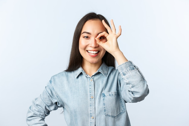 Lifestyle, people emotions and beauty concept. optimistic smiling asian girl looking through okay sign happy, assure everything under control. all good, recommend best product