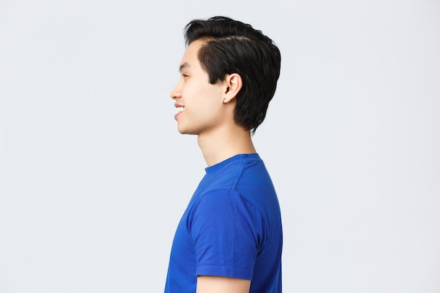 Lifestyle, people emotions and beauty concept. profile shot of asian hipster guy with earring in blue t-shirt, smiling satisfied after making good new hairuct, hairstyle at barbershop