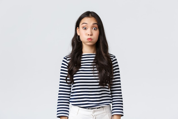 Lifestyle, people emotions and casual concept. confused cute and puzzled girl pouting, searching for solution, holding breath and staring questioned camera, white background