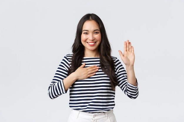 Lifestyle, people emotions and casual concept. honest and sincere cute korean girl making promise, raise on arm and hold hand on heart, smiling while swearing tell truth, give oath