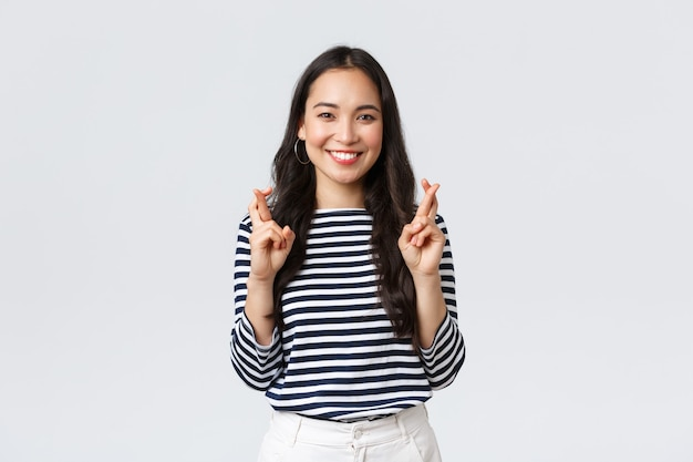 Lifestyle, people emotions and casual concept. hopeful excited cute korean female making wish with fingers crossed, smiling, anticipating positive news, pleading dream come true.