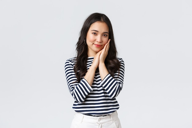 Lifestyle, people emotions and casual concept. tender asian woman with beautiful face, touching cheek gently and gazing camera, advertising beauty product, cosmetics or skincare items