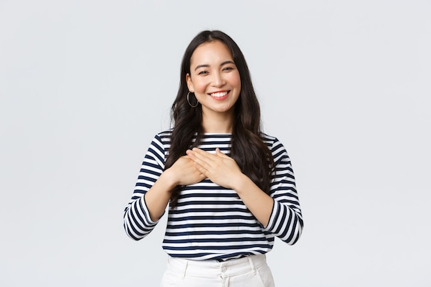 Lifestyle, people emotions and casual concept. touched tender smiling asian woman gladly receive praises, hold hands on heart and grinning thankful, appreciate compliment.