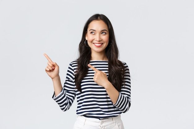 Stile di vita, concetto di emozioni delle persone. eccitata ragazza asiatica di bell'aspetto sorridente soddisfatta di aver trovato un prodotto eccellente, puntando il dito verso la pubblicità e sembrando soddisfatta, consigliando la promozione