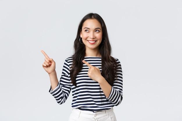 라이프 스타일, 사람들의 감정 개념입니다. 좋은 제품을 발견하고 기뻐하며 웃고 있는 흥분한 잘 생긴 아시아 소녀, 광고에서 왼쪽 손가락을 가리키고 만족스러워 보이는, 프로모션 추천