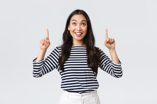 ライフスタイル、人々の感情の概念。優れた製品を見つけて喜んで笑っている、興奮しているハンサムなアジアの女の子、広告に指を向けて満足しているように見える、プロモーションをお勧めします 無料写真