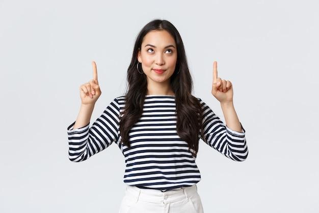 라이프 스타일, 사람들의 감정 개념입니다. 멋진 제품을 발견하고 기뻐하며 웃고 있는 흥분한 잘 생긴 아시아 소녀, 광고를 손가락으로 가리키고 만족스러운 표정, 프로모션 추천