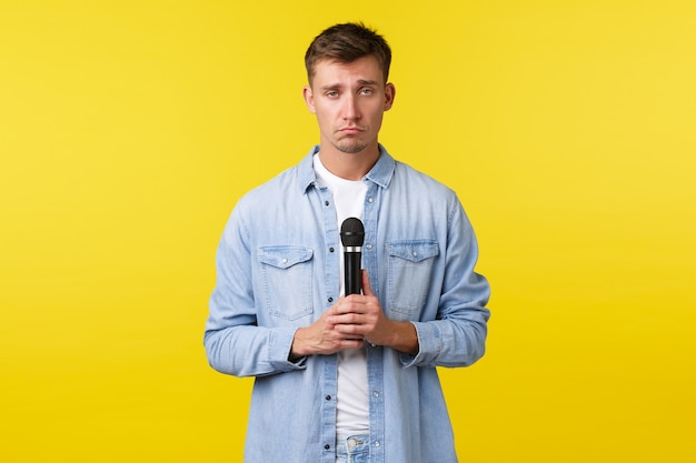 Lifestyle, people emotions and summer leisure concept. gloomy sad blond man, student with microphone looking upset, singing heartbreaking song, standing yellow background.