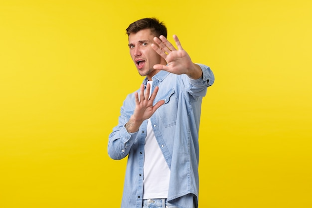 Lifestyle, people emotions and summer leisure concept. scared insecure blond guy trying avoid conflict, asking please stop, defending himself with raised hands, standing yellow background.