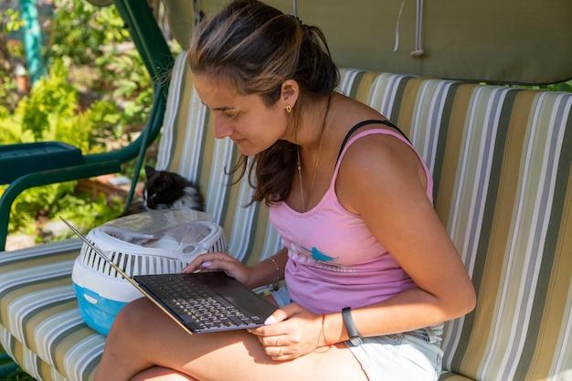 Образ жизни люди девушка работает образование на ноутбуке и слушать музыку для отдыха в открытом саду дома. молодая азиатская женщина, сидящая на качелях с компьютером