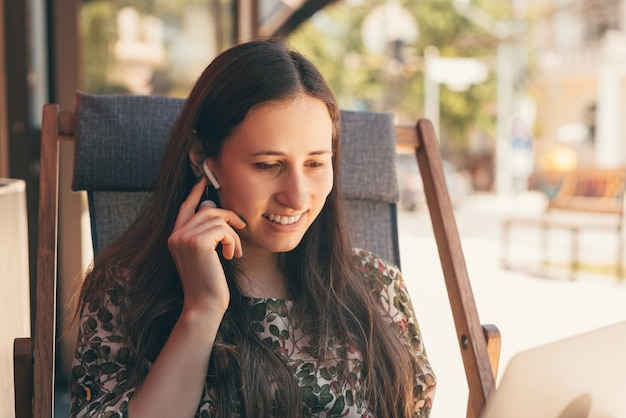 Фотография образа жизни молодой женщины, сидящей на стуле, соединяющем ее вкладыши для ушей.