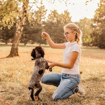 ペットのスパニエル犬と一緒に幸せな少女のライフスタイル写真-自然の中で屋外。