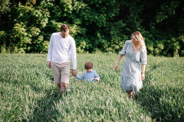 Фотография образа жизни молодой семьи на открытом воздухе в летний день, папа, мама и сын счастливы вместе