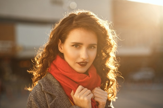 Lifestyle portrait of adorable brunette model with red lips walking down the street in sunny evening