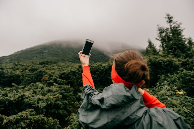 Lifestyle portrait of adventure traveler girl in wet raincoat take selfie on phone high in foggy mountains under rain. young female hiker take self pic on phone