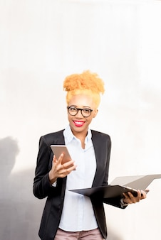 Lifestyle portrait of an african businesswoman in casual suit using phone on the gray wall background