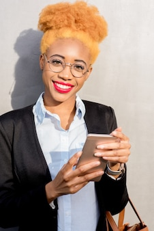 Lifestyle portrait of an african businesswoman in casual suit using smart phone on the gray wall background