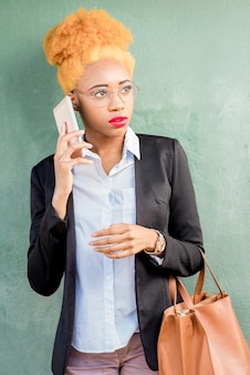 Lifestyle portrait of an african businesswoman in casual suit using smart phone on the green wall background