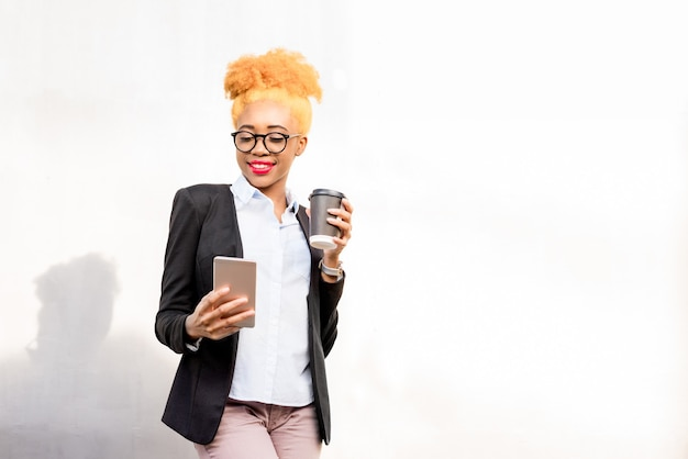 Lifestyle portrait of an african businesswoman in glasses and casual suit standing with phone and coffee cup on the gray wall background