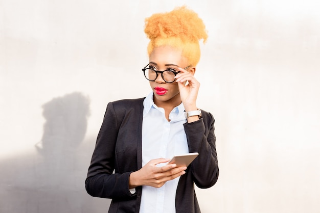 Lifestyle portrait of an african businesswoman in glasses and casual suit standing with phone on the gray wall background