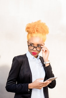 Lifestyle portrait of an african businesswoman in glasses and casual suit standing with phone on the grey wall background