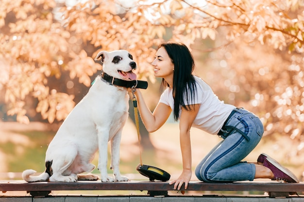 Lifestyle portrait of bautiful young brunette girl standing on knees outdoor and hugging her big lovely white hunting dog. cute stylish sexy woman loves her hound puppy.  pretty teen with pet friends.