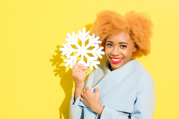 Lifestyle portrait of a beautiful african woman in blue coat with artificial snowflake on the yellow background. autumn concept