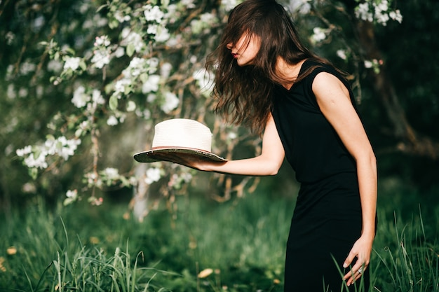 Lifestyle portrait of brunette girl in black dress with straw hat in her hands over blooming apple tree on background.