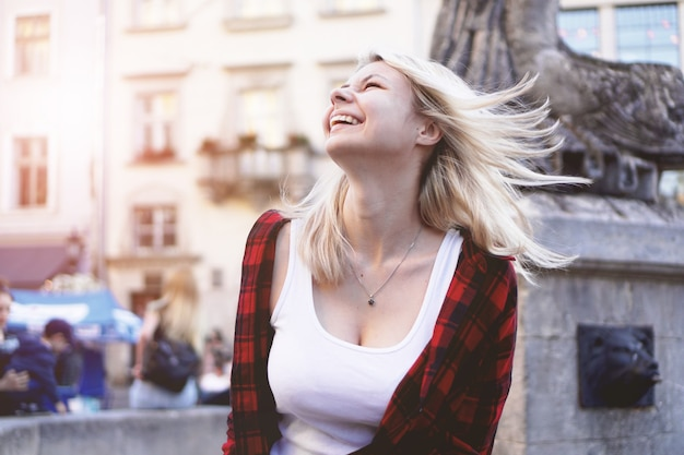 Lifestyle portrait of fashionable happy blonde girl wearing a rock red shirt, white t-shirt having fun outdoors in the city