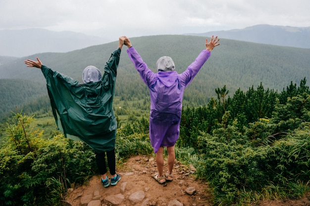 Lifestyle portrait from behind of happy loving traveling couple in raincoats stand on top of mountain in rainy summer day