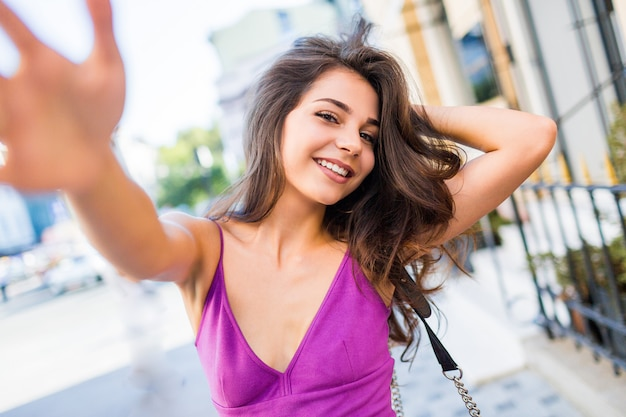 Lifestyle portrait of happy brunette woman in stylish dress making self portrait in city center. cheerful young girl having fun , enjoying summer vacation and weekends.