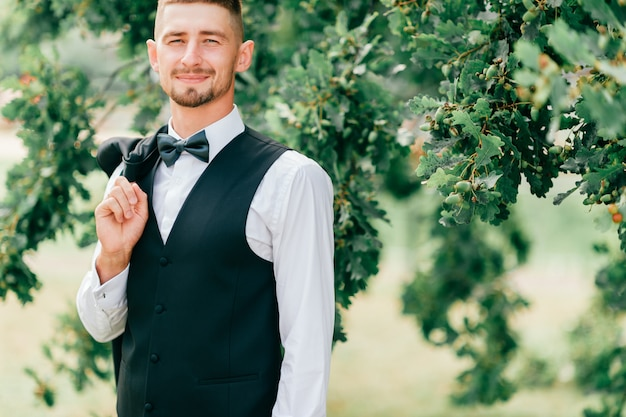Lifestyle portrait of happy groom posing for camera outdoor at nature with oak tree on background. cheerful fiance with smiling face in jakcet, bowtie and white shirt portrait before wedding ceremony